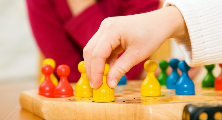 Child playing game with colorful pieces.