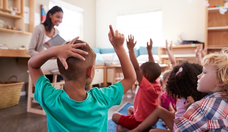 Photo of children with raised hands.